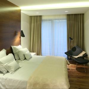 Ścianę za miękkim, tapicerowanym łóżkiem wykończono drewnianym panelem. Równoważy on chłód betonowych ścian. Projekt Katarzyna Kiełek. Fot. Bartosz Jarosz