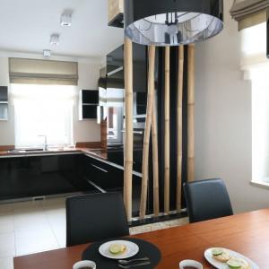 Kuchnię i jadalnię symbolicznie wydziela bambusowa dekoracja umieszczona we wbudowanych donicach. Fot. Bartosz Jarosz.