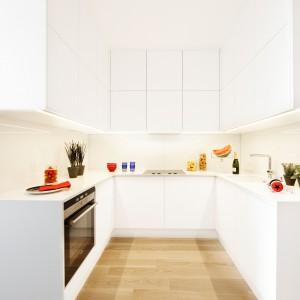 Prosta, biała zabudowa kuchenna w kształcie litery U jest nie tylko elegancka, ale i bardzo pojemna. Liczne szafki górne i dolne zapewniają dużą powierzchnię przechowywania, a obszerne blaty, wykonane z białego laminatu – sporo miejsca do pracy. Szafki kryją w sobie pakowne szuflady oraz dyskretnie maskują sprzęt AGD. Powierzchnia: ok. 4,5 m². Projekt: Maciej Zień. Fot. Ghelamco Poland.