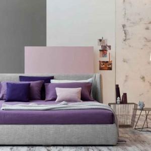 Miękki zagłówek łóżka Basket, dzięki zaokrąglanym bokom delikatnie je otacza. Na zdjęciu tapicerowane w jasnej stonowanej tkaninie w kolorze szarym dostępny jest także w innych wersjach tapicerki. Fot. Bonaldo