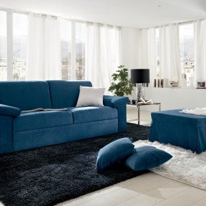 Niebieska sofa i stolik ożywiają białe, nowoczesne wnętrze. Fot. Colombini Casa.