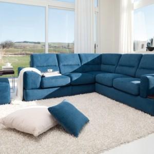 Niebieska sofa pełni funkcję nie tylko siedziska, ale i atrakcyjnej dekoracji białego salonu. Fot. Colombini Casa.
