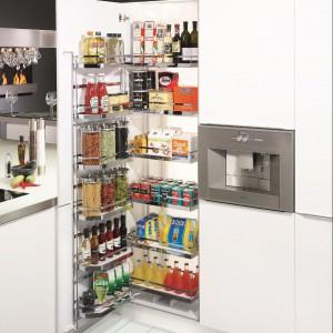 Wysoka szafa cargo umieszczona obok lodówki to świetny pomysł na optymalizację strefy zapasów w kuchni rodziny z dziećmi i nie tylko. Duzi (a także mali) mieszkańcy szybko znajdą potrzebne produkty, a przejrzysta konstrukcja pomoże w utrzymaniu porządku. Na zdjęciu: system Tandem, cargo otwierane jak lodówka, opracowane do szafek 45, 50, 60 cm. Producent: Peka.