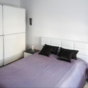 Mała sypialnia urządzona z myślą o parze. Wygodne łóżko oraz pojemna szafa zapewnia komfort użytkowania wnętrza. Projekt: Joanna Ochota. Fot. Bartosz Jarosz.