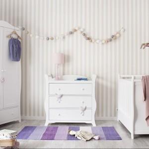 Pasiasty dywan oraz bibeloty w odcieniach fioletu nadają wnętrzu uniwersalny charakter. Fot. TomMebel.