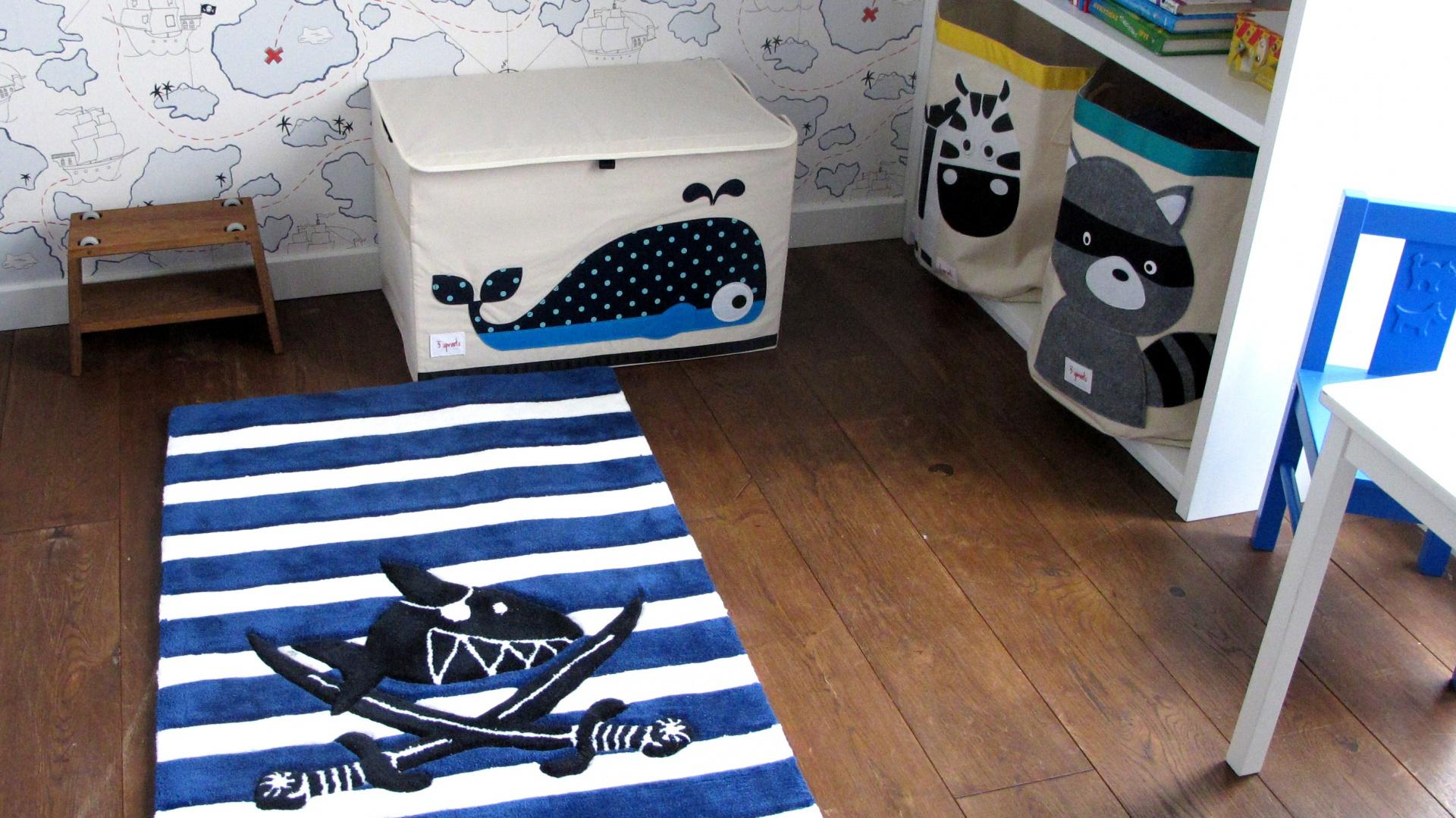 Biało-granatowy dywan z piracką aplikacją oraz skrzynia z wielorybem kreują marynarski charakter pokoju chłopca. Fot. Benjamin Moore.