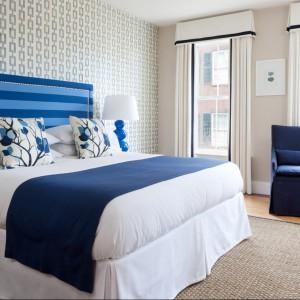 Niebieska, masywna podstawa komponuje się z narzutą oraz wysokim zagłówkiem łózka.Fot.Boutique Nantucket Hotel.