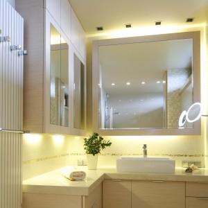 Duża tafla lustra tuż nad umywalką zastąpiła tradycyjne fronty szafki. Podobnie jak mniejsze tuż obok, optycznie powiększa ona przestrzeń łazienki. Projekt Małgorzata Bożyszkowska. Fot. Bartosz Jarosz