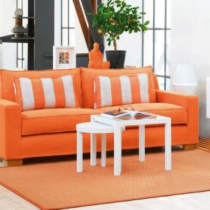 Intensywnie pomarańczowa sofa i nieco bardziej stonowany dywan nadają wyrazisty charakter białemu wnętrzu. Fot. Fogia.