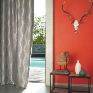 Pomarańczowa ściana jest znakomitym miejscem na ekspozycję neutralnych kolorystycznie dekoracji. Fot. Casadeco.