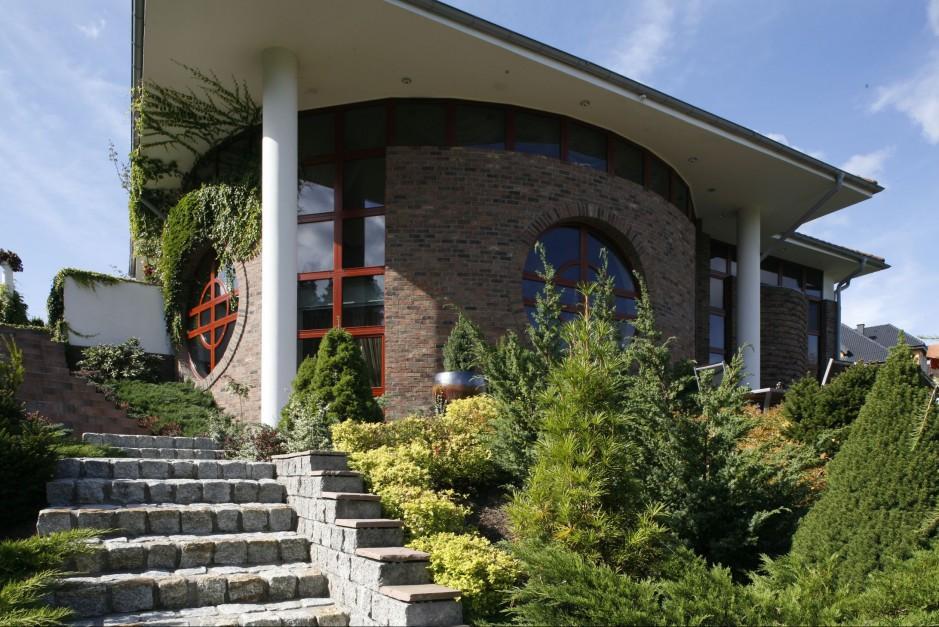 Okrągłe formy ścian budynku stanowią główną ozdobę ogrodu. Fot. Bartosz Jarosz.
