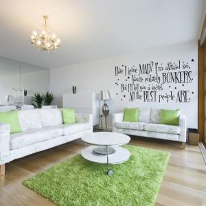 Szaro-białe kanapy ożywia jasnozielony dywan i poduszki dekoracyjne w wiosennym kolorze. Ciekawym urozmaiceniem jest napis na ścianie. Fot. Gift Wrapped and Gorgeous.