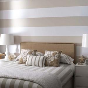 Ciekawym rozwiązaniem jest połączenie dwóch kolorów na jednej ścianie. Poziome, szerokie pasy powiększą optycznie niewielką sypialnię. Fot. Benjamin Moore.