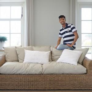 Ratanowa sofa z miękkimi poduchami z kolekcji Riviera Maison. Fot. Riviera Maison.