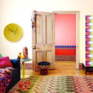Kolorowy dywan, fronty szafy i poduszki na granatowej kanapie zmieniają wnętrze w kolorowy obraz. Fot. RC+D.