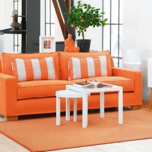 Pomarańczowa sofa i dywan wnoszą do białego pokoju dużo energetycznego ciepła. Fot. Fogia.