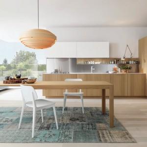 Kuchnia z kolekcji Antis to propozycja od firmy Euromobil. Charakteryzuje się prostotą i elegancją. Zastosowanie frontów o fakturze ładnego, jasnego dębu nadaje jej salonowy charakter. Wysoka zabudowa również wygląda bardziej jak szafa w pokoju niż typowa w kuchni. Funkcjonalny układ mebli w kształcie litery L. W pobliżu kuchni mamy duży stół, który możne być również wygodnym blatem roboczym.