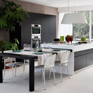 Kuchnia z kolekcji Isola z oferty firmy Moderna Cucine. Centralnym i najważniejszym elementem wnętrza jest duża wyspa, która pełni rolę strefy zmywania i gotowania. Jej przedłużenie stanowi równie duży stół. Miejsce na przechowywanie poza wyspą oferuje także wysoka zabudowa.