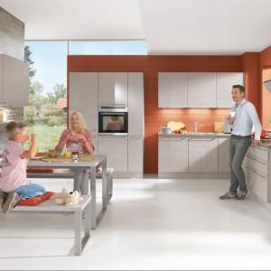 Kuchnia z kolekcji Focus firmy Nobilia. Czerwona ściana stanowi najmocniejszy punkt wnętrza. Fajnie ożywia stonowaną kolorystykę wszystkich pozostałych elementów. Szafki wiszące oraz wysoka i dolna zabudowa zapewniają sporą powierzchnię przechowywania. Mamy też szafki wiszące pozwalające wyeksponować kuchenne akcesoria. Warto zwrócić uwagę na stół, przy którym zamiast tradycyjnych krzeseł ustawiono dwie ławy. Fronty w wysokim połysku.