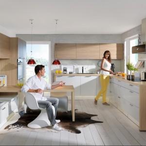 Kuchnia z kolekcji Trend Lack z oferty firmy Nolte Küchen łącząca funkcjonalne rozwiązania z estetycznym wyglądem. Zestawienie białych lakierowanych frontów z drewnianymi nadaje wnętrzu elegancki, ale i ciepły klimat. Meble oferują sporo powierzchnię przechowywania oraz wygodne blaty robocze. Na szczególną uwagę zasługuje miejsce wydzielone na stół.