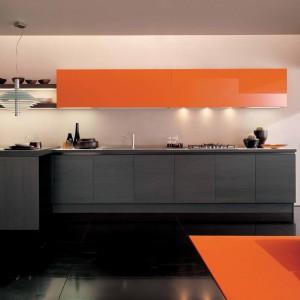 Szafki wiszące w kolorze pomarańczowym doskonale ożywiają kuchnię otwartą na salon. Jest nowocześnie i ciekawie. Dodatki w kolorze pomarańczowy pojawiają się również w części wypoczynkowej. Fot. Euromobile.