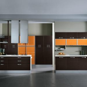 Kolor pomarańczowy zastosowany na frontach kuchennych szafek wprowadza do kuchni zdominowanej przez brązy i szarości dawkę pozytywnej energii. Doskonale ożywia wnętrze. Fot. Mario Cucine.