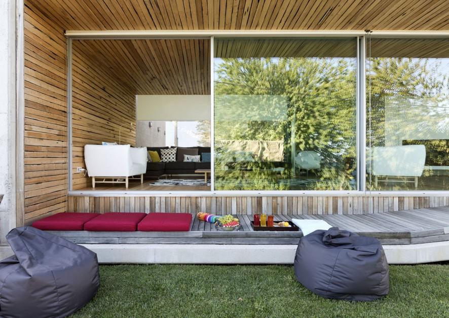 """Projekt domu opiera się na otwartej przestrzeni. Osiągnięto to zarówno poprzez """"otworzenie"""" domu za pomocą przeszkleń, jak i poprzez płynne przejścia między pomieszczeniami. Fot. Inaki Leite, Dezanove House."""