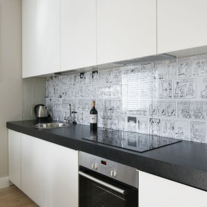 Biała zabudowa kuchenna jest delikatnym tłem, nie ingeruje stylistycznie w przestrzeń salonu. Nowoczesna i minimalistyczna, ale kryje w sobie wszelkie niezbędne sprzęty. Fot. Bartosz Jarosz.