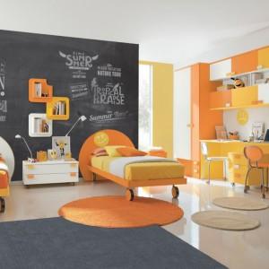 Radosne, pomarańczowo-żółte wnętrze tonuje szary dywan oraz ściana wykończona farbą tablicówką. Fot. Colombini Casa.