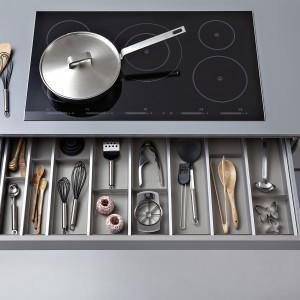 Pod płytą grzejną zaprojektowana została szuflada na sztućce lub narzędzia i drobiazgi kuchenne. Specjalna konstrukcja wkładu umożliwia dopasowanie formatu przegródek do wielkości oraz rodzaju zawartości. Na zdjęciu: kolekcji mebli kuchennych Synthia-C/Ceres-C marki Leicht.