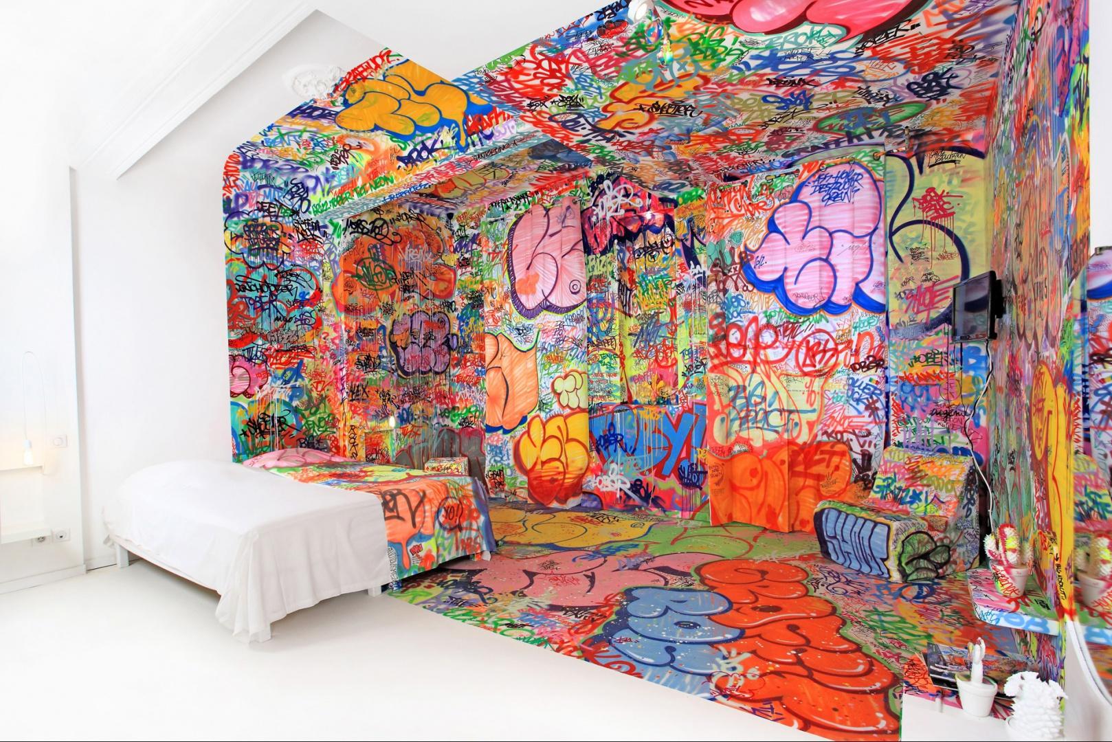 Symetrycznie podzielony pokój na dwie, kontrastowe części to pomysł artystów graffiti. Tilit. Kolorowe, żywiołowe graffiti w zestawieniu z czystą, spokojną bielą tworzy wyjątkowe wnętrze. Proj.Tilt.Fot.Au Vieux Panier.