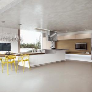 Meble kuchenne z kolekcji AK_03 firmy Arrital. Nowoczesne i idealnie dopasowane do zabudowy w salonie, dzięki czemu otwarta strefa dzienna tworzy spójną, estetyczną całość. Miejsce na jadalnię wygospodarowano przy wyspie. Żółte krzesła stanowią fajny kolorystyczny akcent.