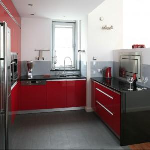 Zabudowa kuchenna wykonana jest z mdf-u lakierowanego na intensywną czerwień. Z barwą frontów kontrastują czarne blaty robocze. Fot. Bartosz Jarosz.