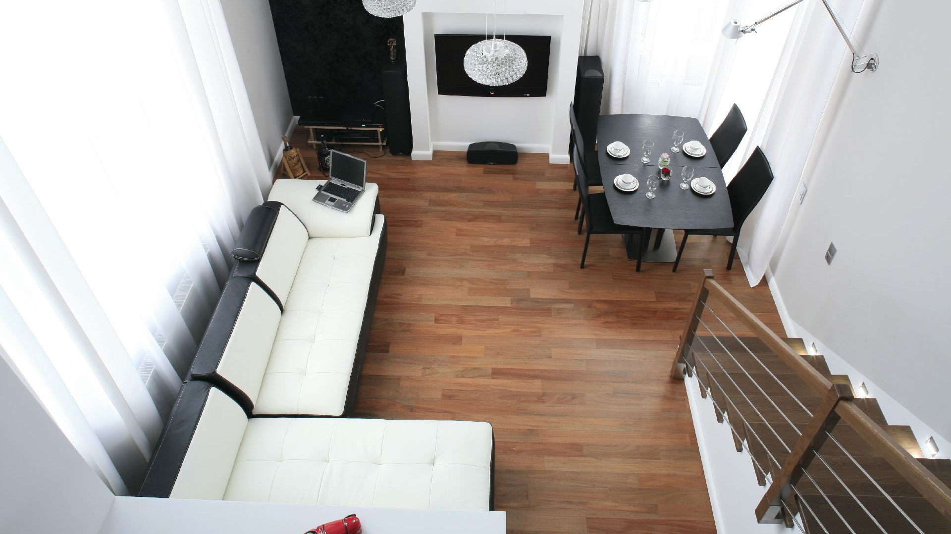 Salon ma niestandardową wysokość – 5,5 m. Nad kuchnią, na antresoli wygospodarowano przestrzeń na gabinet. Fot. Bartosz Jarosz.