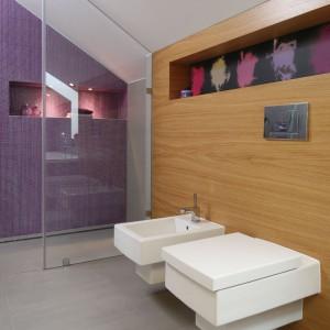 Mozaika w intensywnym fioletowym kolorze ożywia stonowane wnętrze. Doskonale współgra również z ciepłym w odbiorze fornirem dębowym. Fot. Bartosz Jarosz.