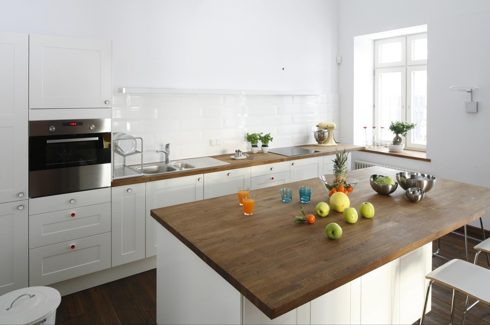 Całkowicie białą kuchnię wizualnie ocieplają drewniane blaty. Aby nie zakłócać tej