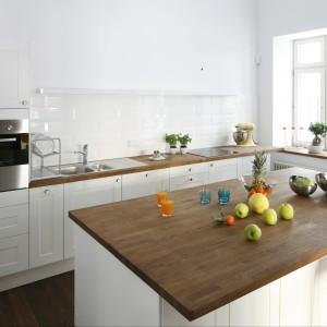 """Całkowicie białą kuchnię wizualnie ocieplają drewniane blaty. Aby nie zakłócać tej """"sterylności"""" wnętrza zrezygnowano tu z szafek górnych na rzecz długiej, wąskiej półeczki także w kolorze białym. Projekt Konrad Grodzinski. Fot. Bartosz Jarosz."""