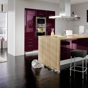 Meble z kolekcji IP2800 z oferty firmy Impuls. Fronty lakierowane na wysoki połysk w kolorze intensywnego fioletu. Pięknie łączą się z drewnianym blatem i ciemną podłogą. Całość prezentuje się niezwykle elegancko.