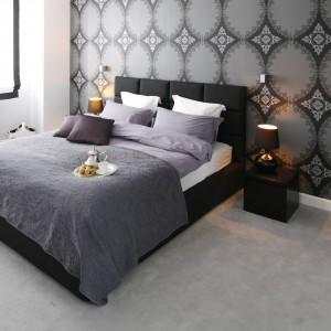 Charakterystyczna, wzorzysta tapeta stanowi doskonałe tło dla czarnego, tapicerowanego łóżka oraz szafek nocnych. Proj.Magdalena Smyk. Fot. Bartosz Jarosz.