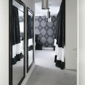Na przeciwko garderoby znajdują się dwa, prostokątne lustra w czarnych ramach. Ramy tworzą przyjemny kontrast z jasnymi ścianami. Proj.Magdalena Smyk. Fot. Bartosz Jarosz.