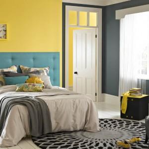Intensywny, żółty kolor wyznaczający strefę łóżka, kontrastuje z turkusowym zagłówkiem. W zestawieniu z pozostałymi, szarymi ścianami tworzy spójną, ciekawą kompozycję. Fot.Dulux.