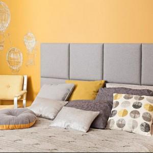 Przygaszony, żółty odcień ściany dobrze komponuje się z jasnymi szarościami. Na zdjęciu jednolity, modułowy zagłówek Made for bed. Fot.Made for bed.