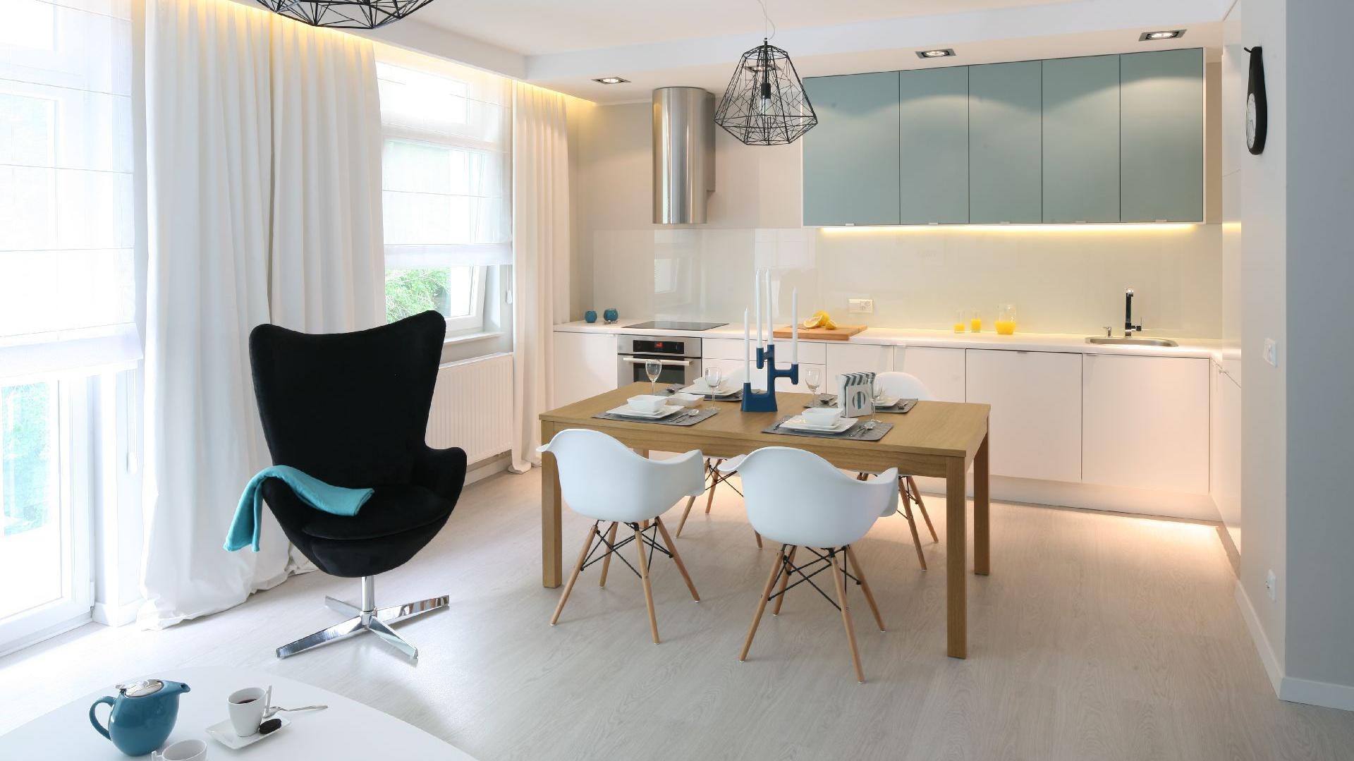 Otwarta część dzienna z nowoczesną kuchnią, w której minimalistyczne białe szafki pięknie podkreślają turkus górnej zabudowy. Nad blatem zamontowano taflę hartowanego szkła, które od spodu polakierowano na biało. W otwartej jadalni stanął stół IKEA, do którego dobrano krzesła – klasyki designu projektu Charlesa i Ray Eamesów. Wyposażenie: zabudowa kuchenna MDF lakierowany na mat IKEA / nad blatem hartowane szkło lakierowane od spodu na biało / piekarnik Mastercook / okap Faber / oświetlenie w zabudowie Italux. Fot. Bartosz Jarosz.
