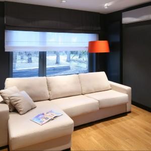 Ciemna ściana złagodzona została kanapą w jasnym odcieniu oraz roletą okienną. Dodatkowo wprowadzono barwny akcent w postaci oprawy lampy stojącej, która wraz z drewnianą podłogą ociepla wnętrze. Fot. Bartosz Jarosz.