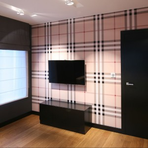 To jedyne pomieszczenie, w którym pojawia się deseń w postaci kraciastej tapety ściennej. Motyw powtarza się w układzie i kolorystyce półek regału wykonanego na zamówienie według pomysłu projektantki. Fot. Bartosz Jarosz.