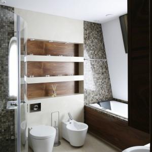 W przestronnej łazience główne miejsce zajmuje niestandardowych rozmiarów kabina prysznicowa wykonana na zamówienie. Wanna, będąca tu głównie miejscem do relaksu, została umieszczona na całej długości skosu poddasza. Projekt KPP Studio. Fot. Bartosz Jarosz.