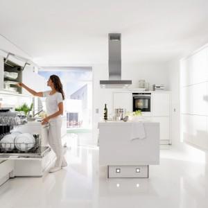 Meble z kolekcji Star z oferty firmy Nolte Küchen. W tej kuchni zdecydowanie króluje biel. W tym kolorze są zarówno fronty mebli, blaty, jak i podłoga. Wyspa znajduje się na środku pomieszczenia  – pomiędzy zabudową z jednej i z drugiej strony. Zapewnia miejsce zarówno na wygodne na gotowanie (płyta grzejna) oraz na przechowywanie.