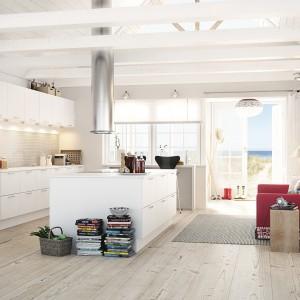 Meble z kolekcji Mono firmy HTH. Wyspa jest na tyle duża, że można na niej gotować i przygotowywać posiłki. Ma również sporo pojemnych szafek. Białe fronty mebli ociepla drewniana podłoga.