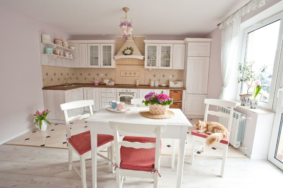 Pastelowe kolory i meble w prowansalskim stylu nadają kuchni sielski, spokojny charakter. Dla podkreślenia smaku – odrobina malinowej czerwieni w dodatkach. Kuchnia i jadalnia znajdują się w otwartej strefie dziennej. Projekt: właściciele. Fot. Agnieszka Węglarz.