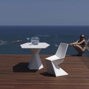 Meble dedykowane do jadalni - zarówno tej na zewnątrz, jak i we wnętrzu o bardzo zgeometryzowanej formie z kolekcji Vertex zaprojektowanej dla marki Vondom. Dwa stoły - duży lub mniejszy (na zdjęciu) dostępne są w białym i czarnym kolorze, krzesła - bogatej gamie intensywnych kolorów.